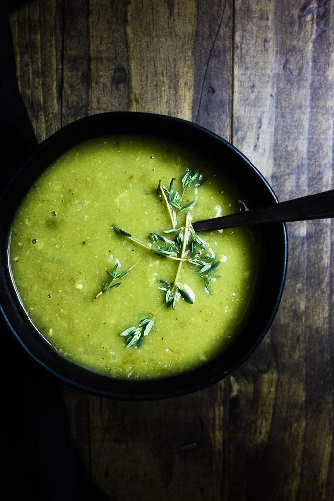 instant pot split pea soup in a bowl with thyme and a spoon