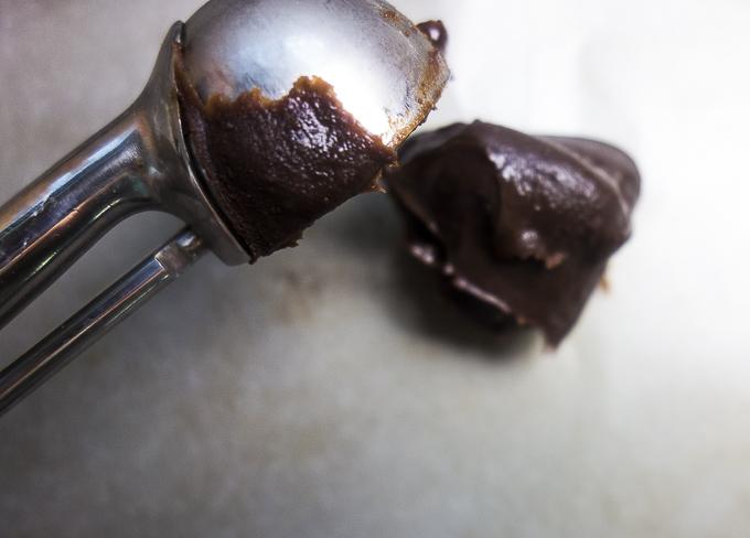 spooning dark chocolate truffles mixture onto surface