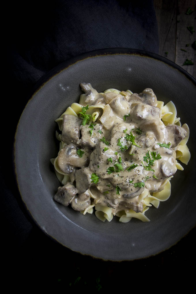 creamy beef stroganoff in a bowl garnished with parsley