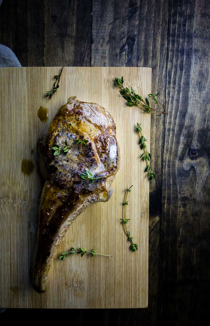 seared veal chops on a cutting board with thyme and truffle butter