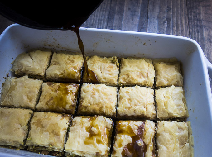 pouring syrup over hot baklava