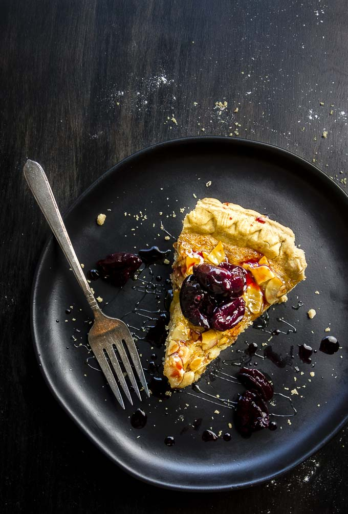 piece of simple almond tart on a plate with fork and candied cherries