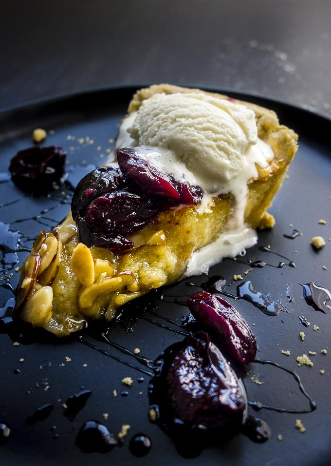 simple almond tart topped with candied cherries and ice cream