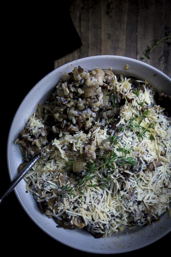 This Wild Rice Stuffing with Mushrooms is packed full of rich flavor and made with all different kinds of mushrooms, butter, garlic, fresh herbs, and of course, a sprinkle or two of parmesan cheese - perfect for your Thanksgiving dinner! #wildricestuffing #thanksgivingstuffing #mushroomstuffingthanksgiving sides | thanksgiving stuffing  stuffing recipes | wild rice and mushroom stuffing | mushroom dressing | wild rice and mushroom pilaf
