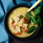 bowl of creamy soup with chicken, vegetables and garnished with basil and a gold spoon