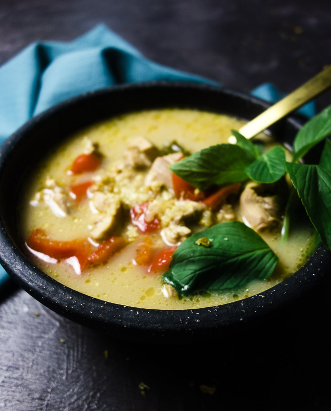 bowl of creamy chicken soup with quinoa basil and red peppers