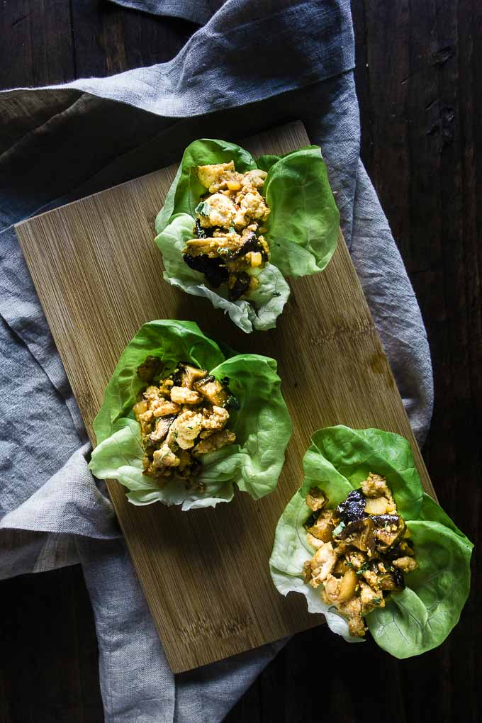 ground chicken in cups of lettuce on a wood board