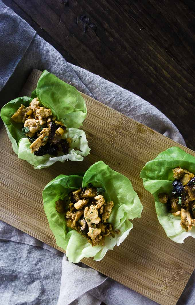 3 lettuce cups with a ground chicken mixture on a board