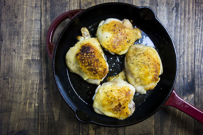 browned chicken thighs in a skillet