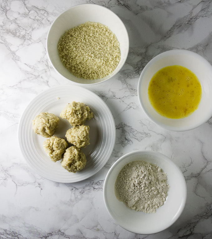 balls of risotto, breadcrumbs, flour and eggs in bowls