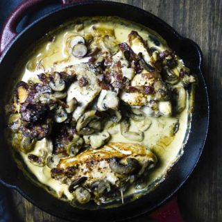 stuffed chicken in a skillet covered in creamy sauce