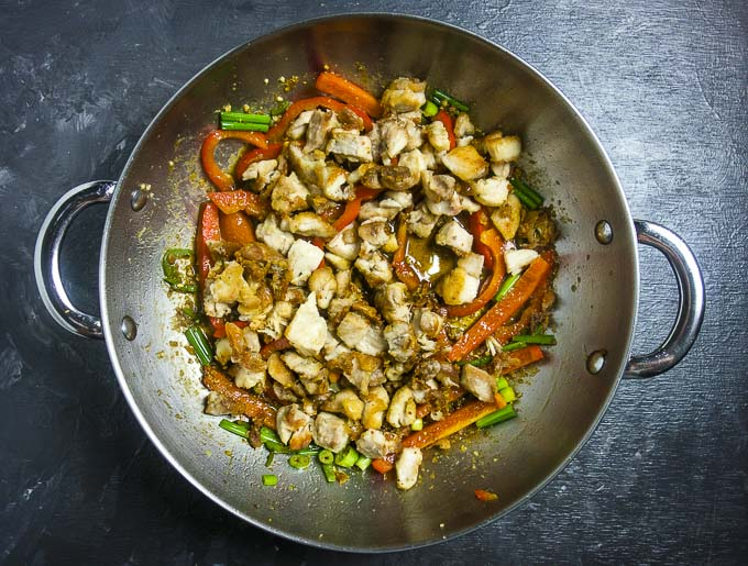 chicken mixed with vegetables in a saute pan with sauce