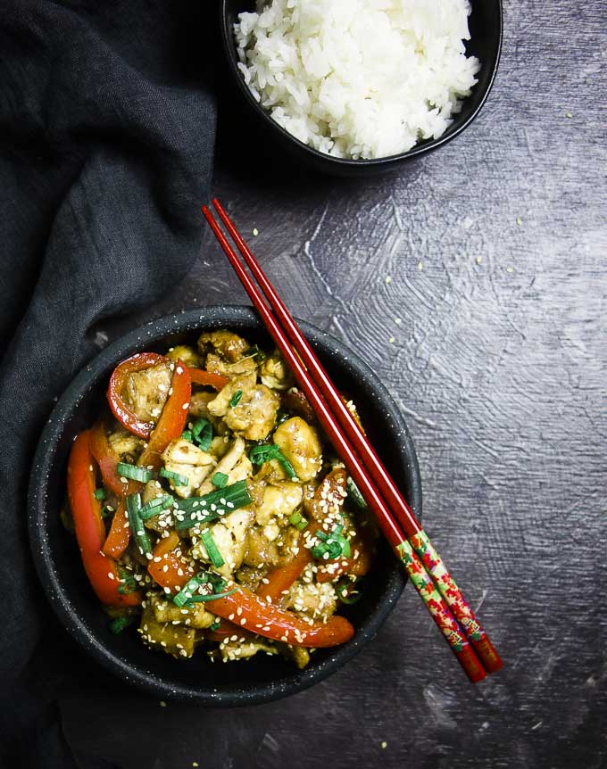 chicken coated in sauce with sesame seeds and green onions on top - bowl of rice on the side