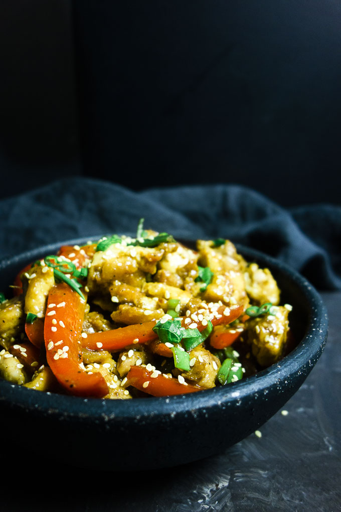 side view of stir fry chicken in a bowl with vegetables and sesame seeds