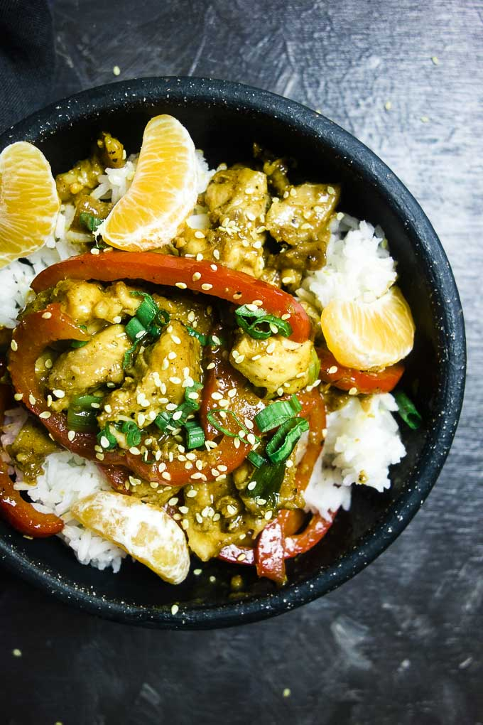 chicken pieces in sauce over rice with orange segments and sesame seeds