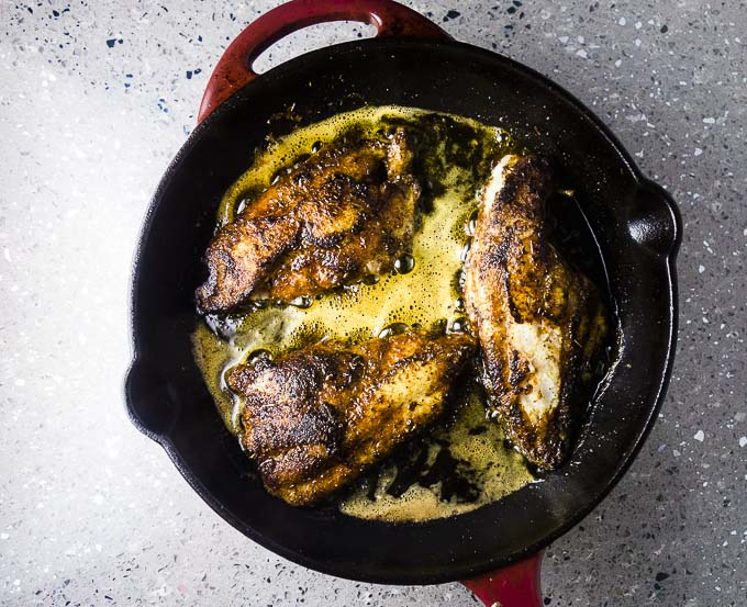 seasoned catfish being fried in a cast iron skillet