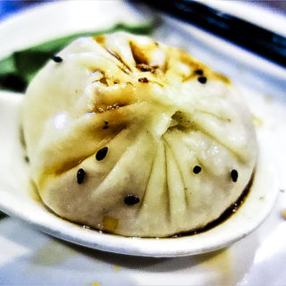 soup spoon holding a dumpling with sesame seeds