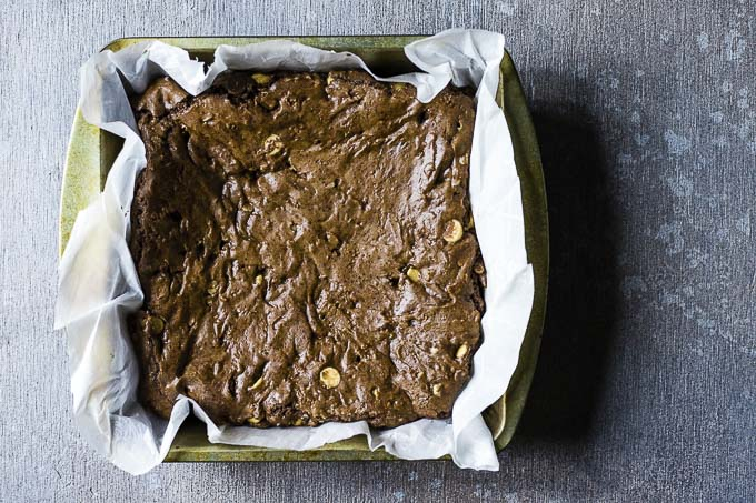cooked brownies in a parchment paper lined square baking dish