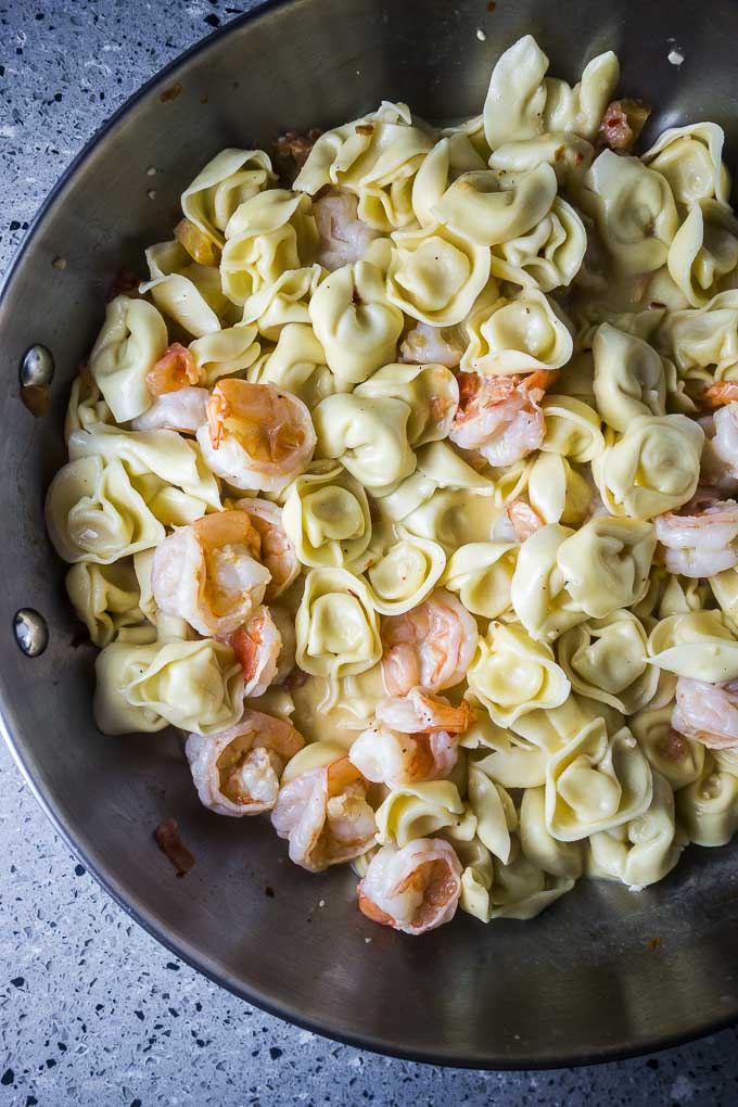 Tortellini with creamy shrimp sauce in a skillet