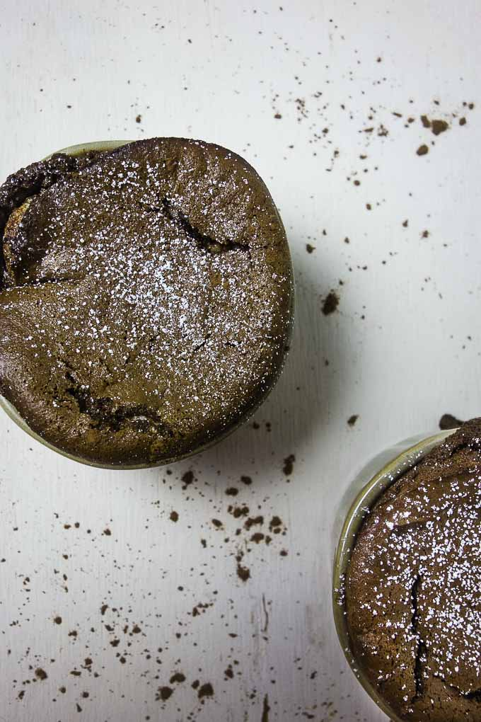 close up view of a chocolate souffle in a ramekin dusted with powdered sugar