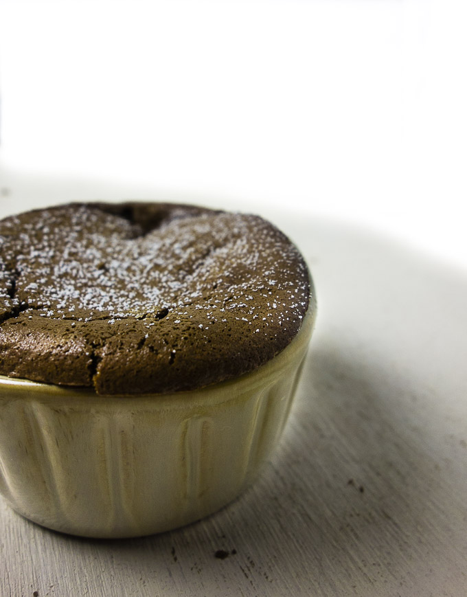 side view of a chocolate souffle in a ramekin dusted with powdered sugar