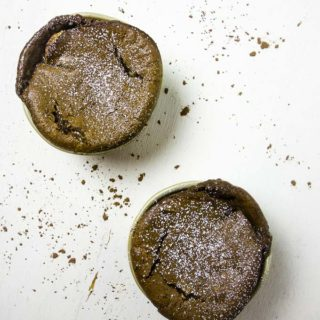 2 chocolate souffles on a white background with cocoa powder