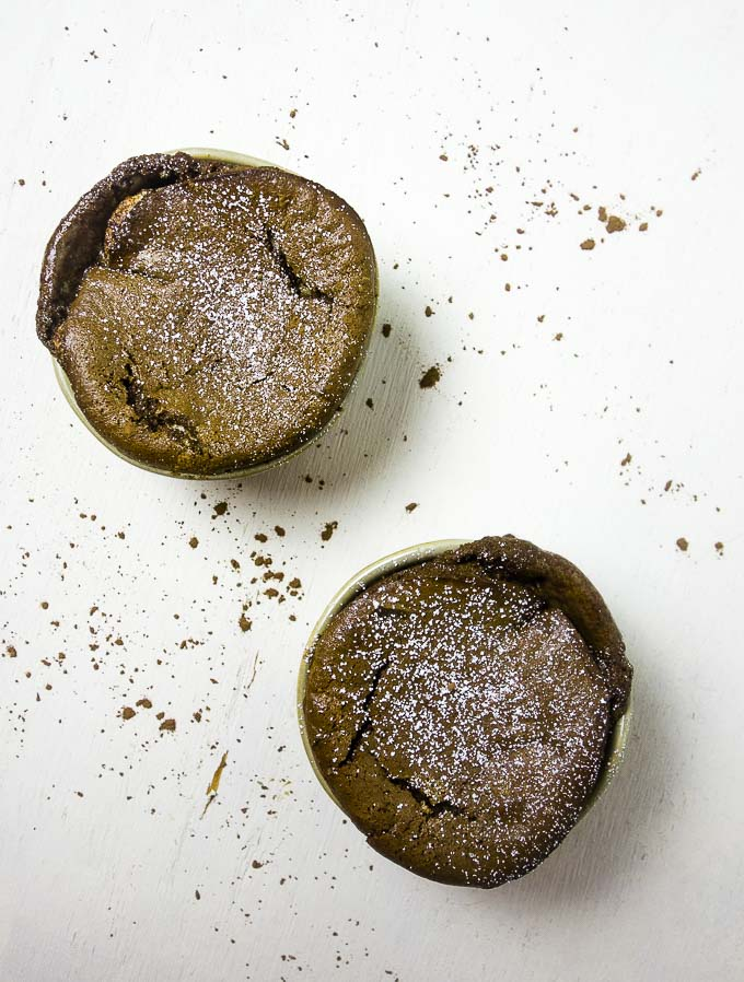 2 chocolate souffles on a white background with cocoa powder and powdered sugar dusted