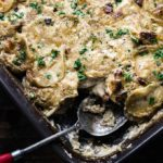 creamy baked scalloped potatoes in a baking dish with a spoon