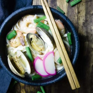 bowl of udon noodle soup with clams, shrimp and green onions with chopsticks