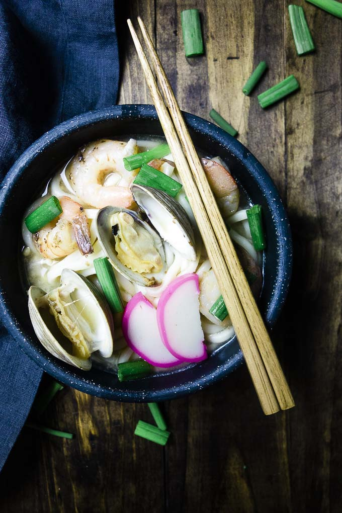 noodle soup with clams, shrimp and green onions in a bowl with chopsticks