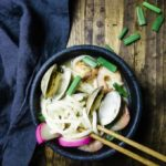 udon noodle soup with clams, shrimp and green onions with chopsticks