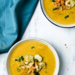 2 bowls of orange soup with crawfish and croutons on top