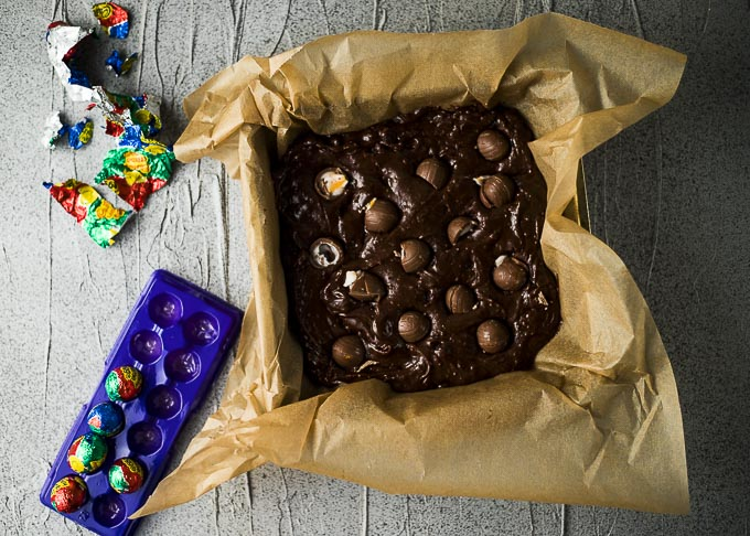 cadbury eggs placed in brownie batter