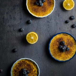 3 creme brulees on a surface with blueberries and lemon
