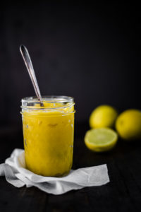lemon curd in a glass jar with a spoon
