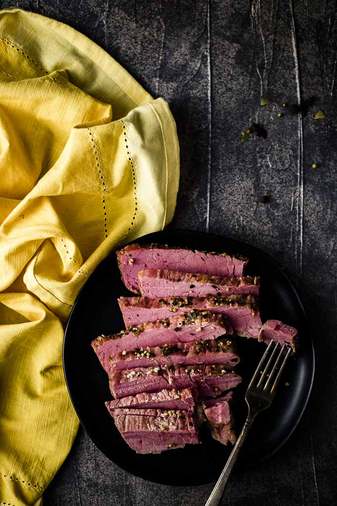 plate of corned beef slices with piece on a fork