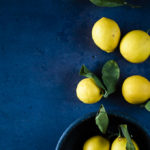 lemons in a bowl and on a surface with leaves on