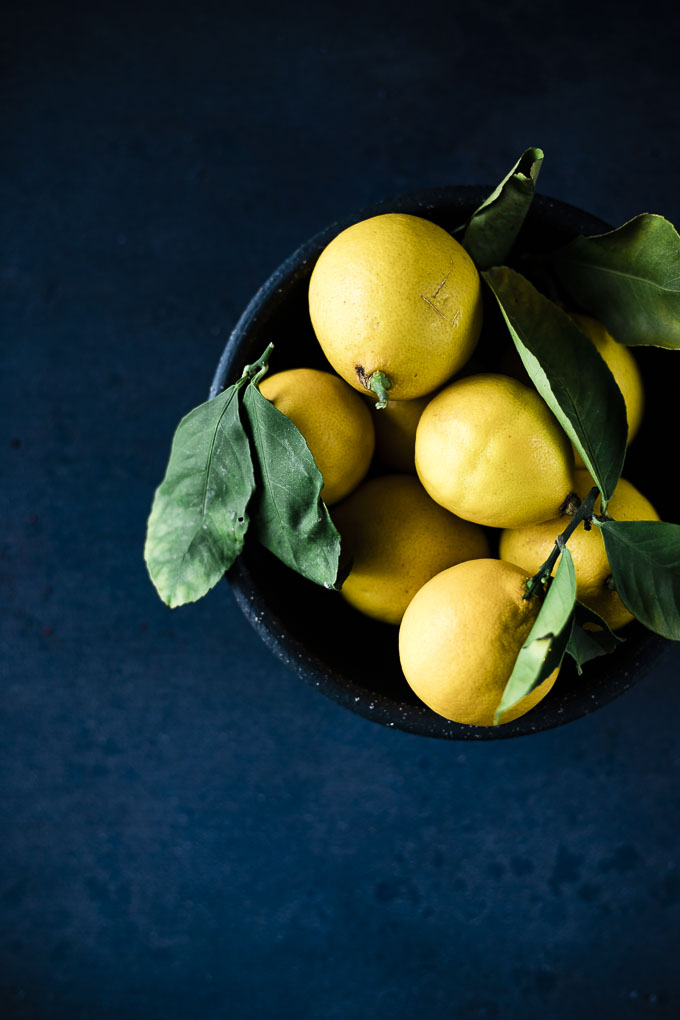 bowl of lemons with green leaves