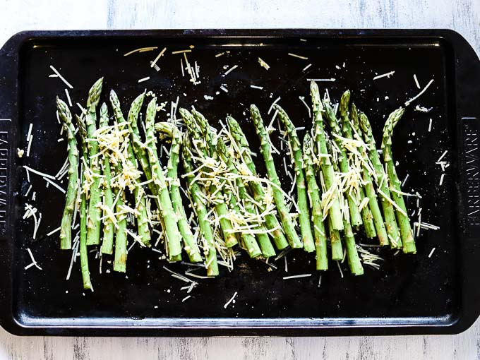 asparagus on a baking sheet covered in cheese