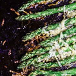 close up of asparagus with crispy browned cheese on top
