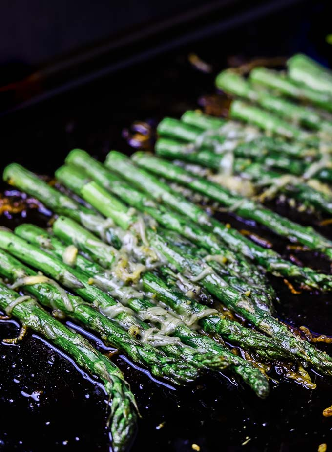 close up of asparagus stalks covered in cheese on a baking sheet