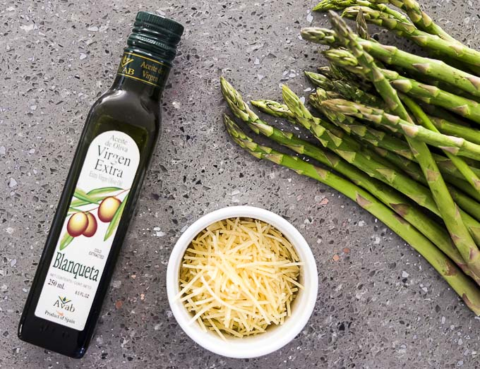 olive oil, parmesan cheese and asparagus on a surface