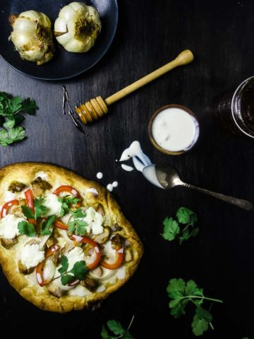 naan flatbread pizza with red peppers, chicken, cilantro and white sauce - roasted garlic in the background