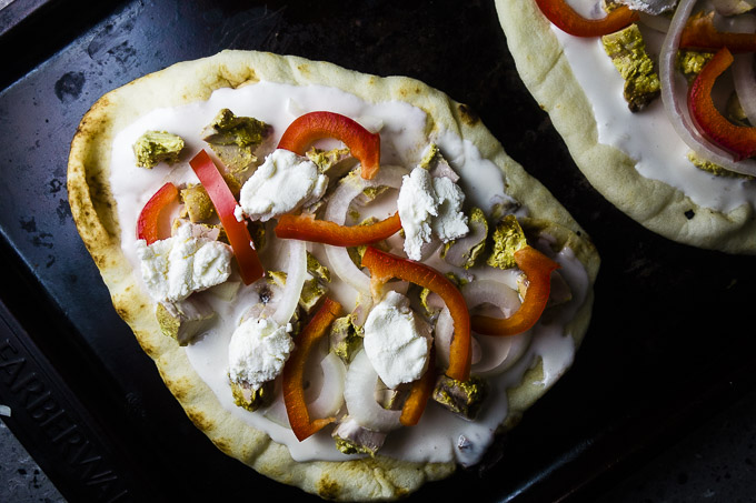 naan bread with white sauce, cheese, red peppers and chicken