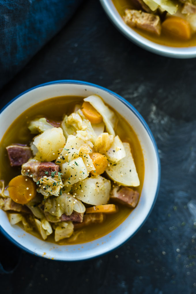 bowl of soup with carrots, potatoes and corned beef garnished with parsley