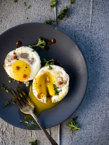 egg cups on a plate with runny egg yolk top down view