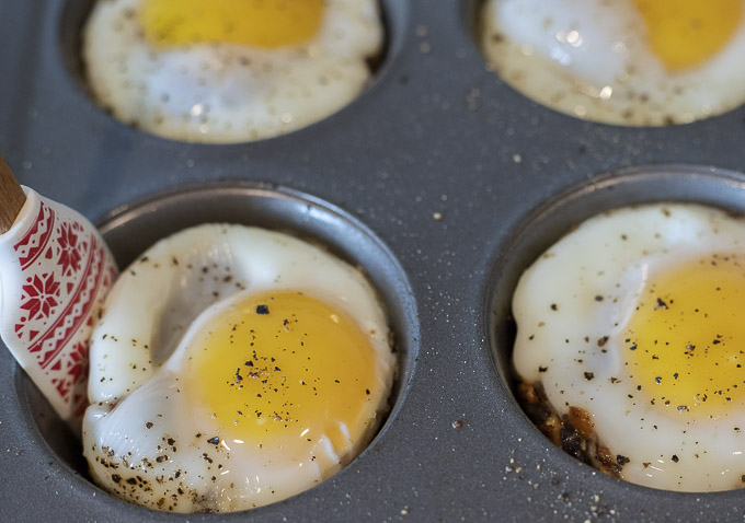 using a spatula to get an egg cup out of muffin tin