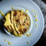 cheese souffle in a ramekin drizzled with hollandaise