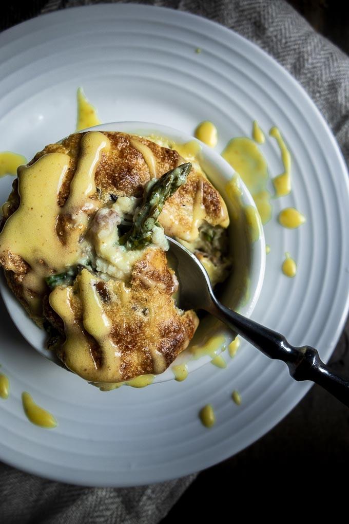 spoon dug into a ramekin of cheese and asparagus souffle