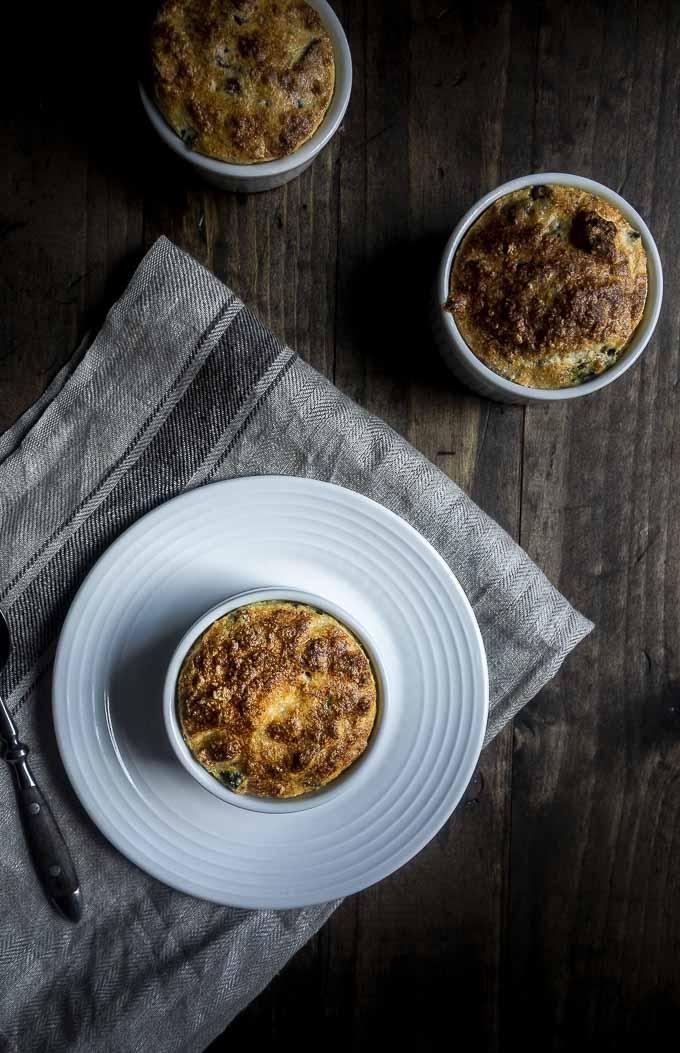 3 cheese souffles in ramekins on a board